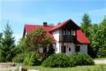 Dom  z czerwonym dachem wśród krzewów