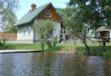 Dom biały nad jeziorem. Widoczny pomost