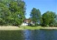 Dom nad jeziorem - widok z jeziora - dużo drzew i czcin
