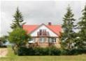 Dom z czerwonym dachem wśród drzew