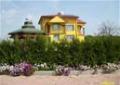 Żółty dom z wieżą wśród pól